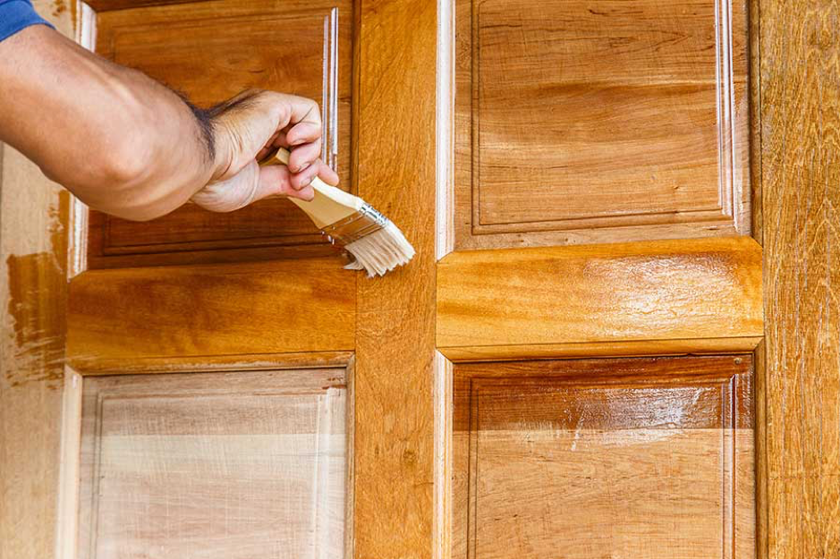 mans hand using a paint brush to apply finish to an oak door
