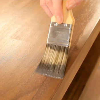 an image of someone holding a paint brush applying wax to a door